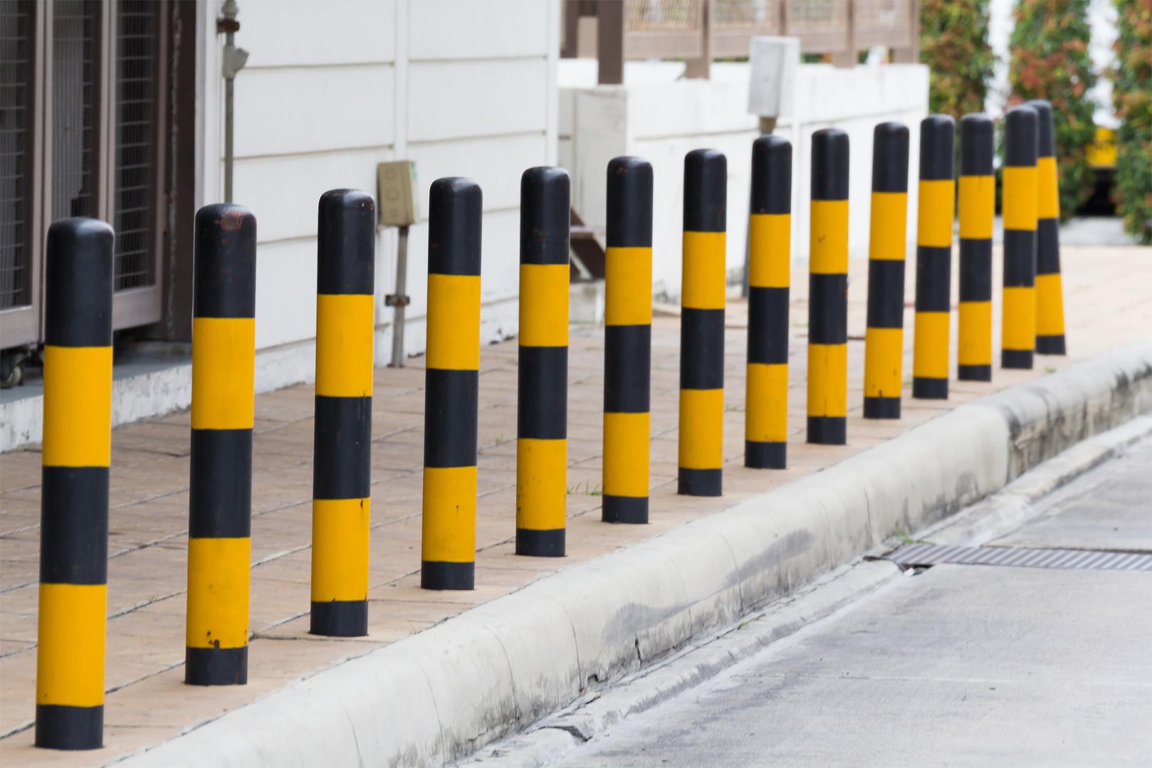 yellow and black steel bollards on footp