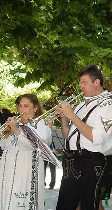 Two trumpet players in lederhosen and dirndl playing outside.