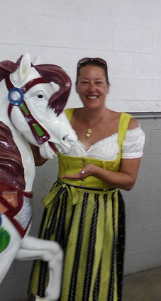 Woman in dirndl with a carousel horse.