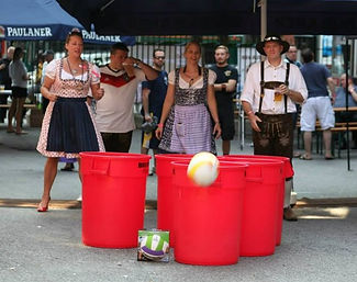 Girls in dirndls and guys in lederhosen playing a giant version of Beirut with trash cans and a volleyball, often referred to as Beer Pong.