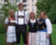 Three women in dirndls and one man in lederhosen poing for a picture.