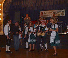 Polka band playing to a crowd in lederhosen and dirndls.