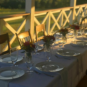 Sunset dinner setting on farmhouse porch