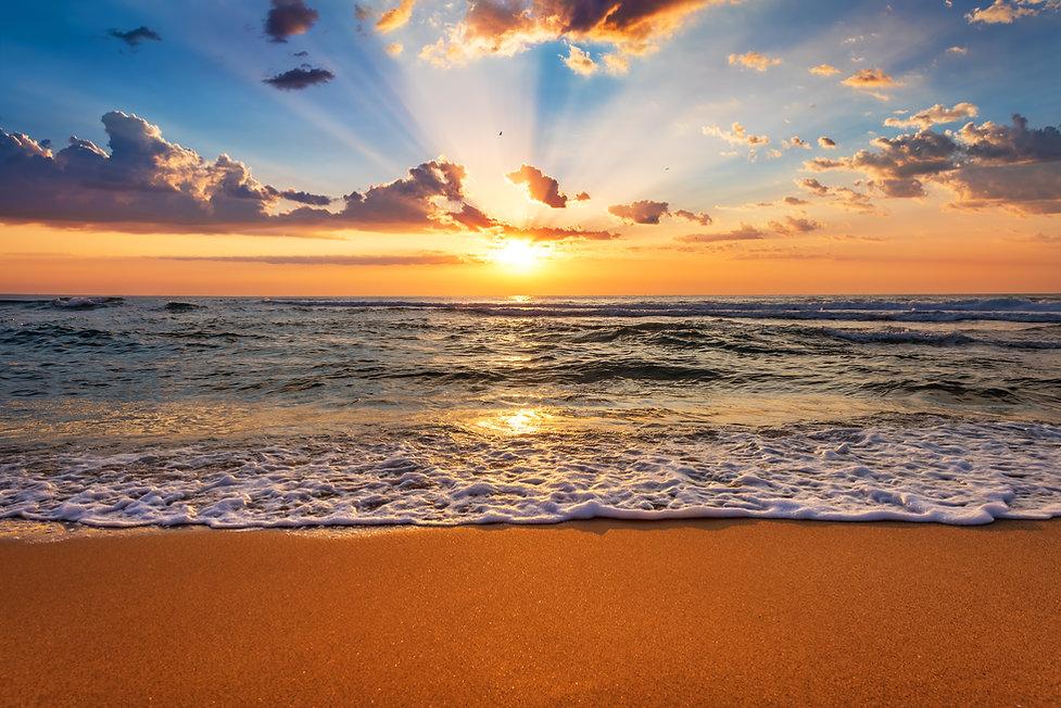 Colorful ocean beach sunrise with deep b