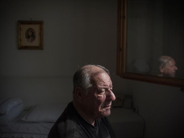"""Sacco river Valley, Colleferro (Rome). Mr.Mattei is a former worker of a chemical factory who, during the years of activity, was in charge of carrying casks containing toxic garbage to the areas/fields where they were buried. As it happened to many locals, the beta-HCH, a highly carcinogenic Lindane product was found in Mattei's blood. He is currently president of the """"asbestos-lindane victims association"""". In this photo-portrait Mattei sitting on the bed in his bedroom. ---- Valle del Sacco, Colleferro (Roma). Luigi Mattei, ex operaio della BPD di Colleferro (industria chimica), durante gli anni di attività era addetto al trasporto dei fusti contenenti rifiuti tossici nei terreni in cui venivano seppelliti. Come molti abitanti della zona, nel suo sangue è stata rilevata la presenza del beta-hch. Attualmente è presidente dell' """"Associazione Vittime Lindano e Amianto""""."""