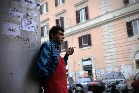 All'esterno di un'attività commerciale, uomo ritratto durante un momento di pausa dal lavoro.