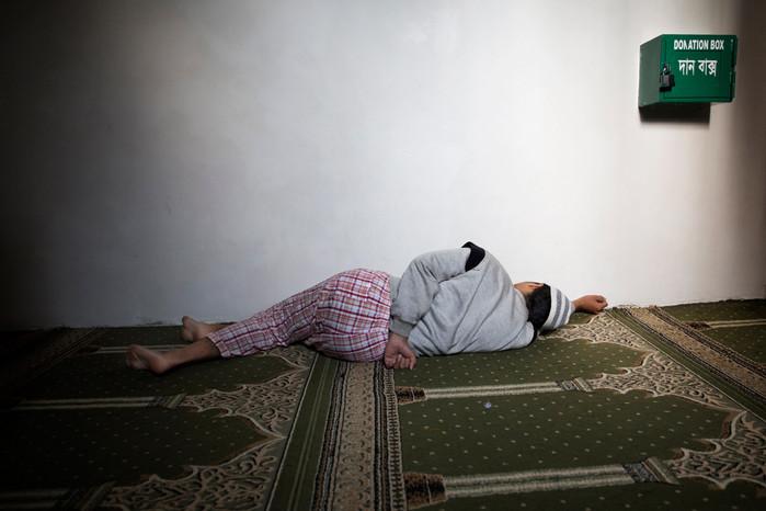 Giovane si riposa all'interno di una moschea approfittando di una pausa lavoro. Gli orari lavorativi spesso coprono l'intera giornata ed in diversi casi vanno oltre.