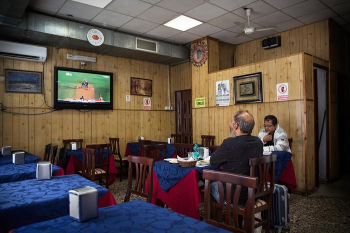 Clienti di un ristorante etnico osservano una partita di cricket, sport nazionale di tutto il subcontinente indiano.