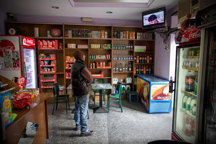 Giovane bengalese guarda un programma televisivo indiano all'interno di un bar.