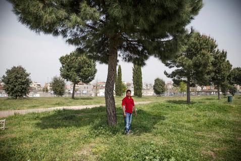 Centocelle, giovane si ripara dalla calura sotto un albero del parco.