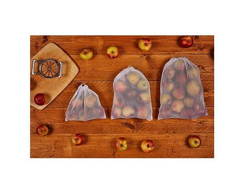 drei Obstbeutel bzw. Gemüsebeutel gefüllt auf einem Holztisch