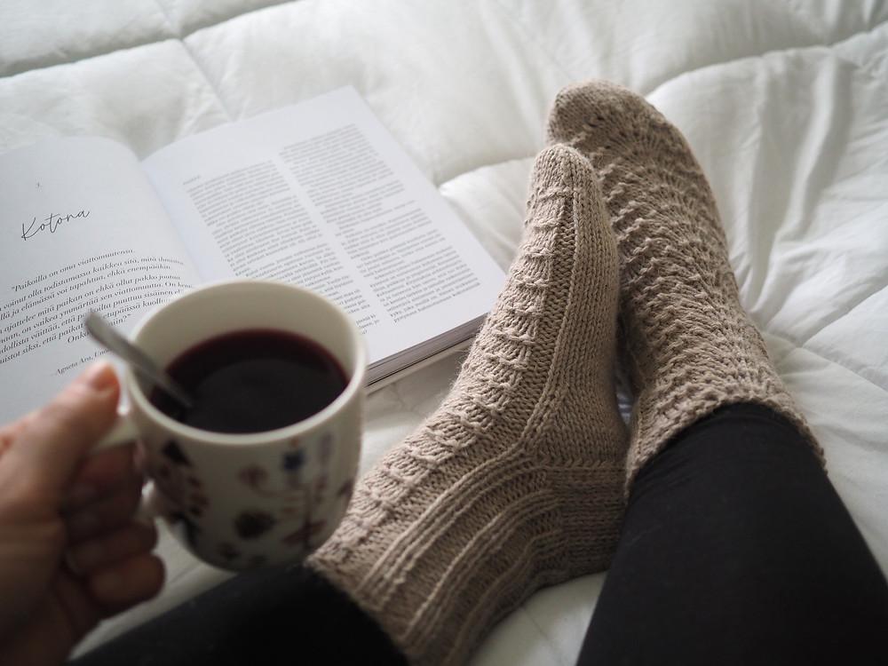 villasukat, kirja ja teekuppi