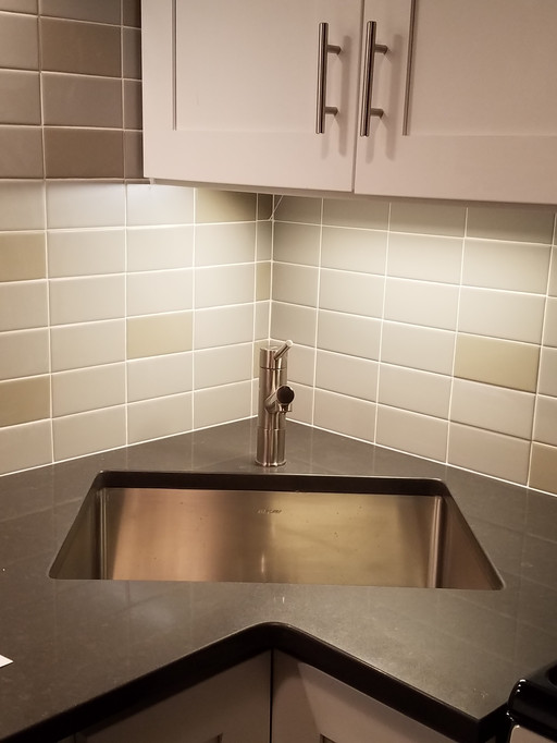 The corner sink helps maximize the small kitchen by opening up additional counter and cabinet storage space
