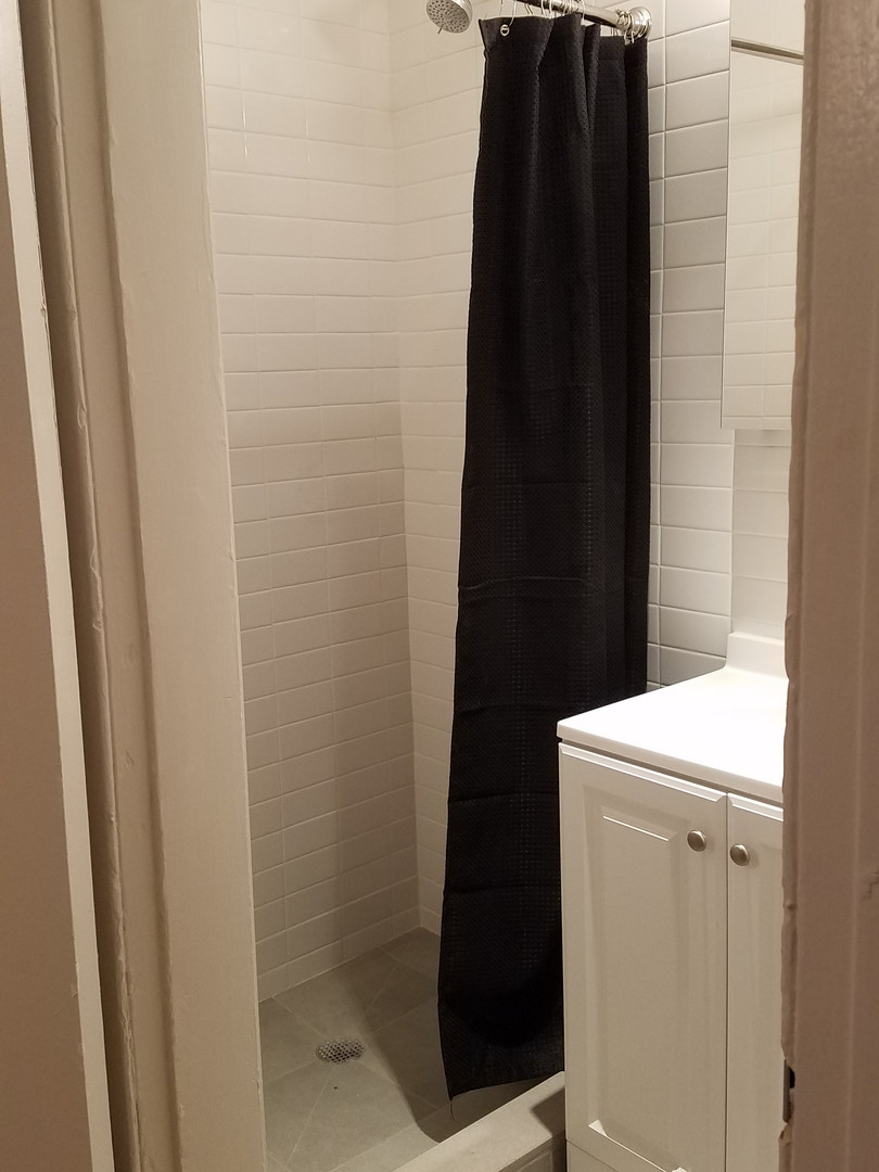 Replacing the tub with a walk-in shower helps open up a very cramped bathroom