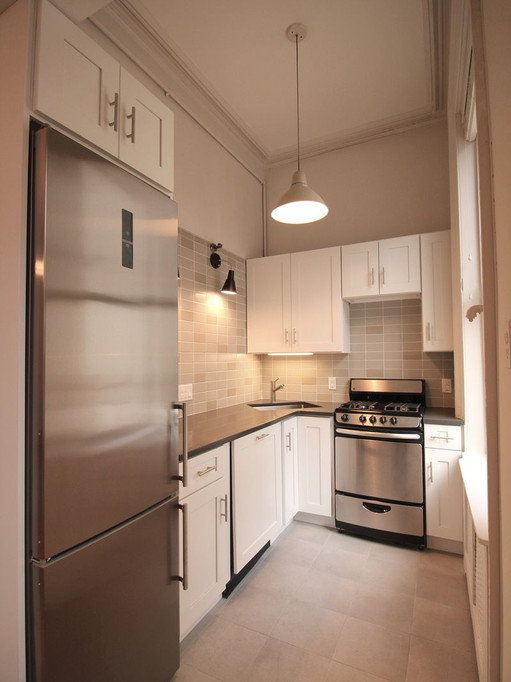New kitchen layout is open, connected to the main living space, and takes fulla advantage of the existing window and natural light