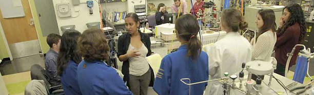 Aradhna Tripati is seen standing, in a laboratory. She is speaking with a group of 7 students who have formed a semi-circle in front of her. They are listening to Aradhna, facing away from the camera. Some are wearing labcoats. Lab machinery is seen in the foreground and background.