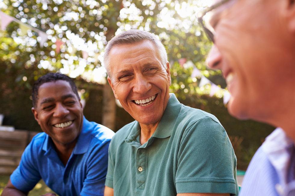 Mature Male Friends Socializing In Backy