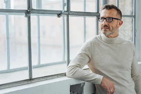 Thoughtful man wearing glasses standing