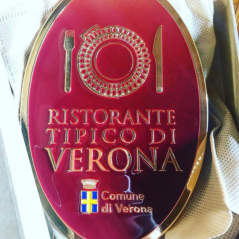 Ristoranti Tipici di Verona's claque affixed on the Caffe Monte Baldo's wall.