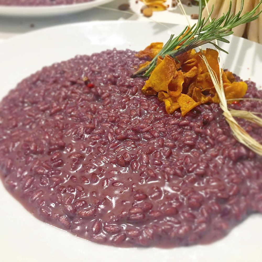 """Risotto all'amarone della Valpolicella is an iconic recipe of Verona corsine. Made with the premium Amarone della Valpolicella red wine poured into our local"""" Vialone Nano"""" white rice. Try it in our osteria Caffè Monte Baldo whit a bit of Monte Veronese local cheese, paired with a tasty glass of Amarone"""