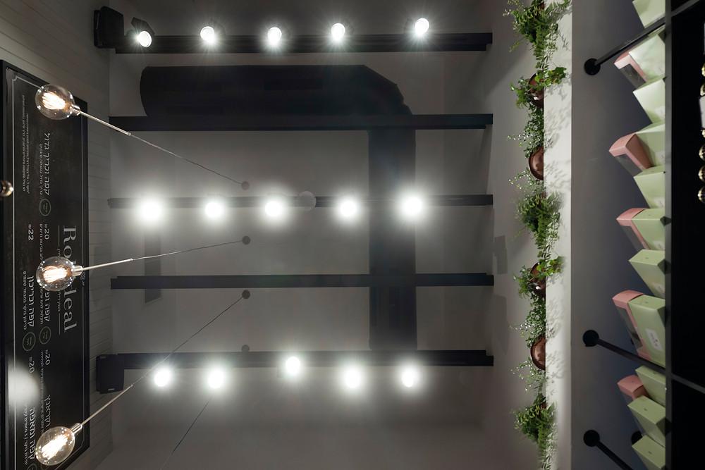 """תאורה תכנית בגוון שחור ממוקמת ע""""ג קורות ברזל חשופות ותאורה דקורטיבית- גופי תאורה מפליז המשתלשלים מהתקרה הקונסטרוקטיבית של המקום עם נורות פחם המוסיפות חמימות"""