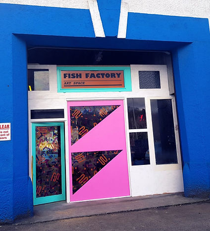 The front of the Fish Factory Art Space showing it's pink and green doors and orange sign