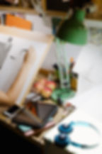 An artist's desk viewed from above while they draw a bird. Crative clutter, appes and desk lamp make a cosy scene