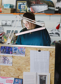 One of te Fish Factory Artists at work at her desk in the open plan studio space. Creative clutter and desk lamps form a frame around her concentrated face.