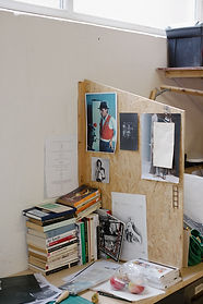 An artist's desk ace in our shared studio shows a pile of art books and posters pinned up for inspiration