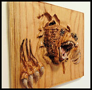 Wooden carving of grizzly breaking through Wood