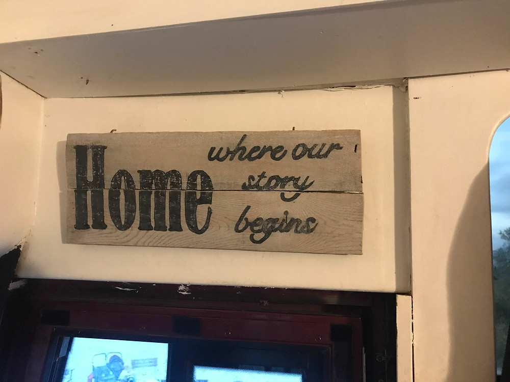 Sign above RV door that says, Home, Where our story begins.