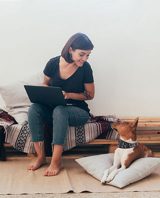 Woman working from home sitting on a bench and looking down at dog
