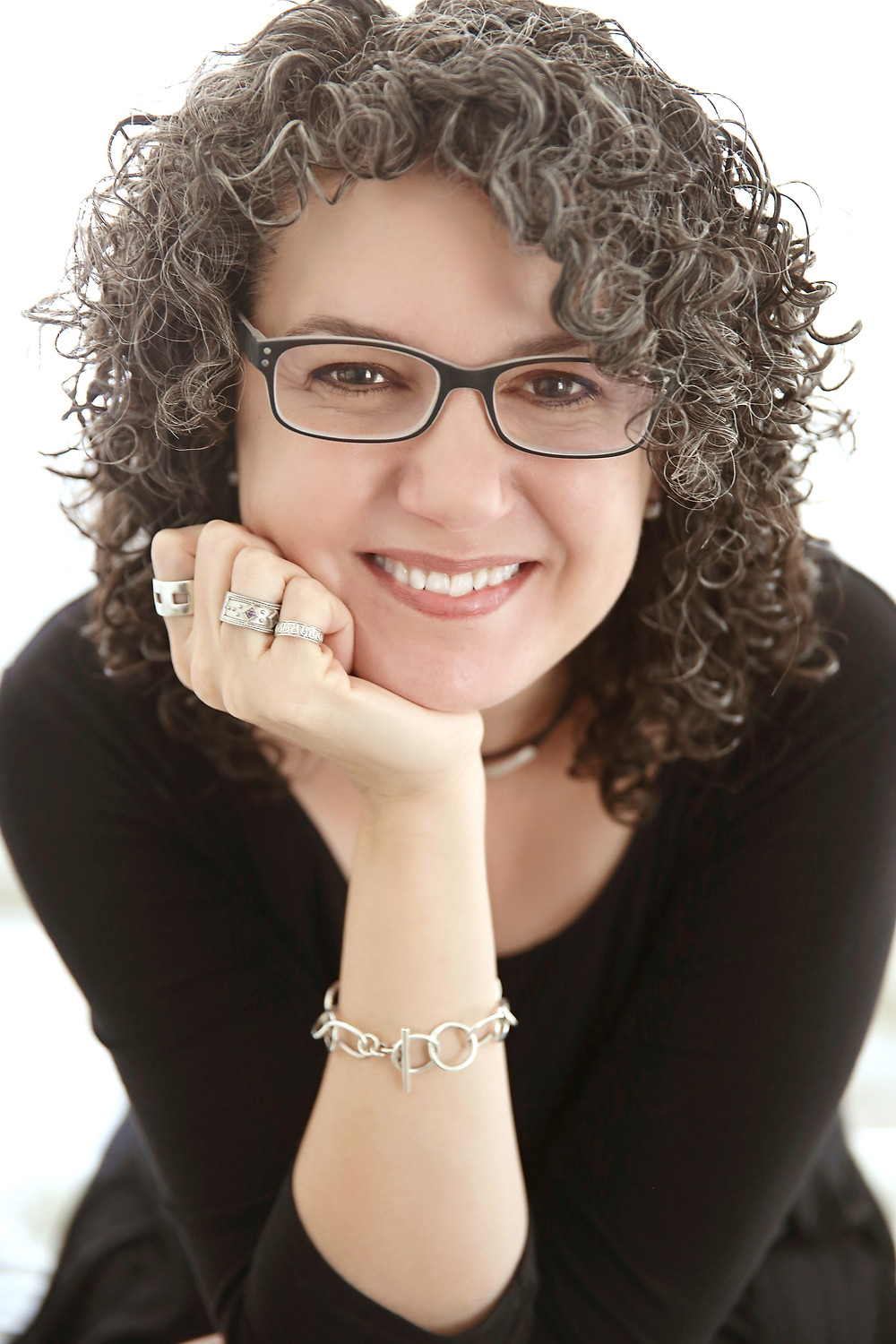 women headshot in studio wearing glasses salt and pepper hair and smiling with rings on
