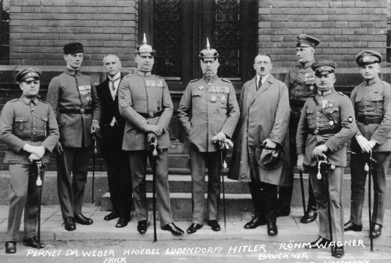 Hoffmann, Heinrich: Adolf Hitler (cuarto por la derecha) posando junto con  los demás acusados por el Putsch de Múnich durante su juicio, 1924, fotografía, Bundesarchiv.