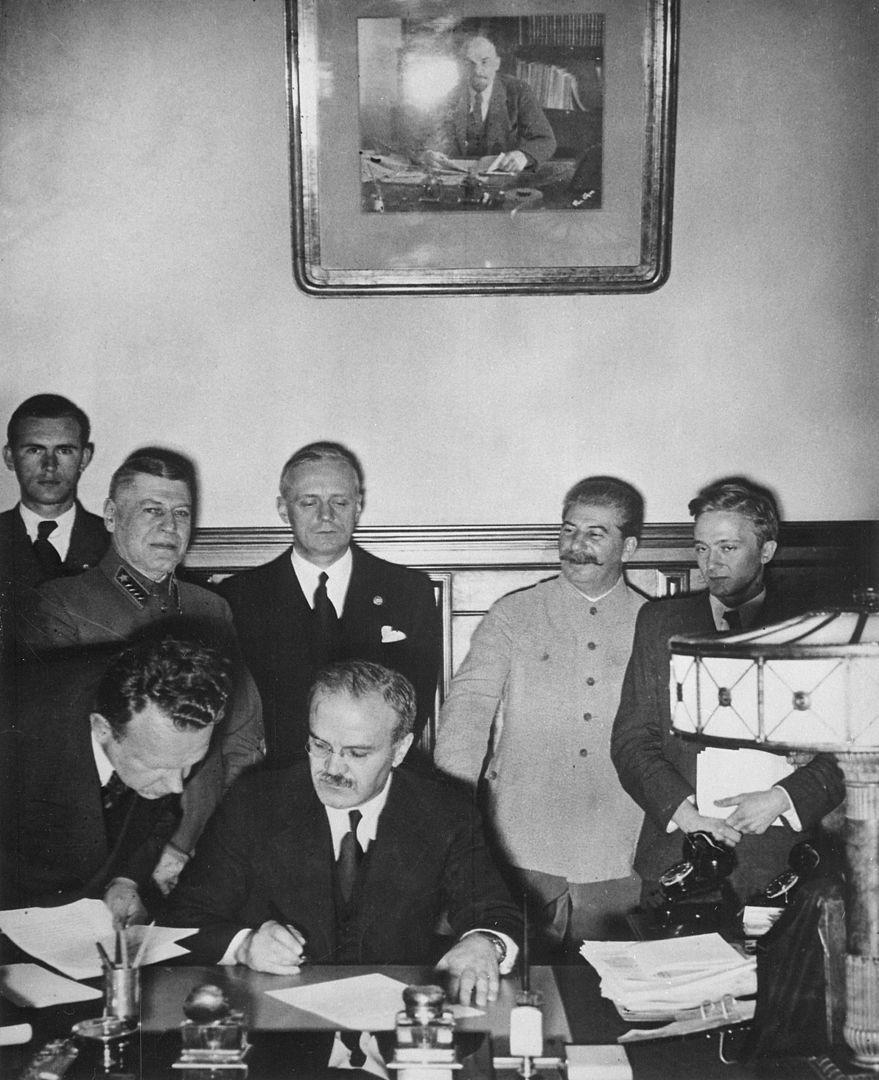 """Firma del Tratado de No Agresión o """"Pacto Ribbentrop-Molotov"""" en Moscú; sentado y a punto de firmar está el comisario del pueblo de asuntos exteriores soviético Vyacheslav Molotov, de pie tras él el ministro de asuntos exteriores alemán Joachim von Ribbentrop y a la izquierda de éste Iosif Stalin, 1939, fotografía, fondos del TSGAKFD."""