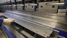 Worker in factory at metal skip machine