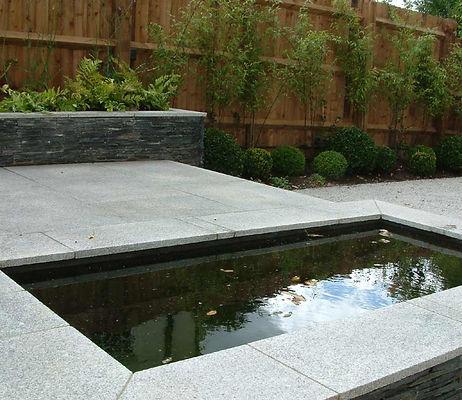 Walling faced with slate.  Pool stone walling box balls. Mark Langford Garden Design Buckinghamshire