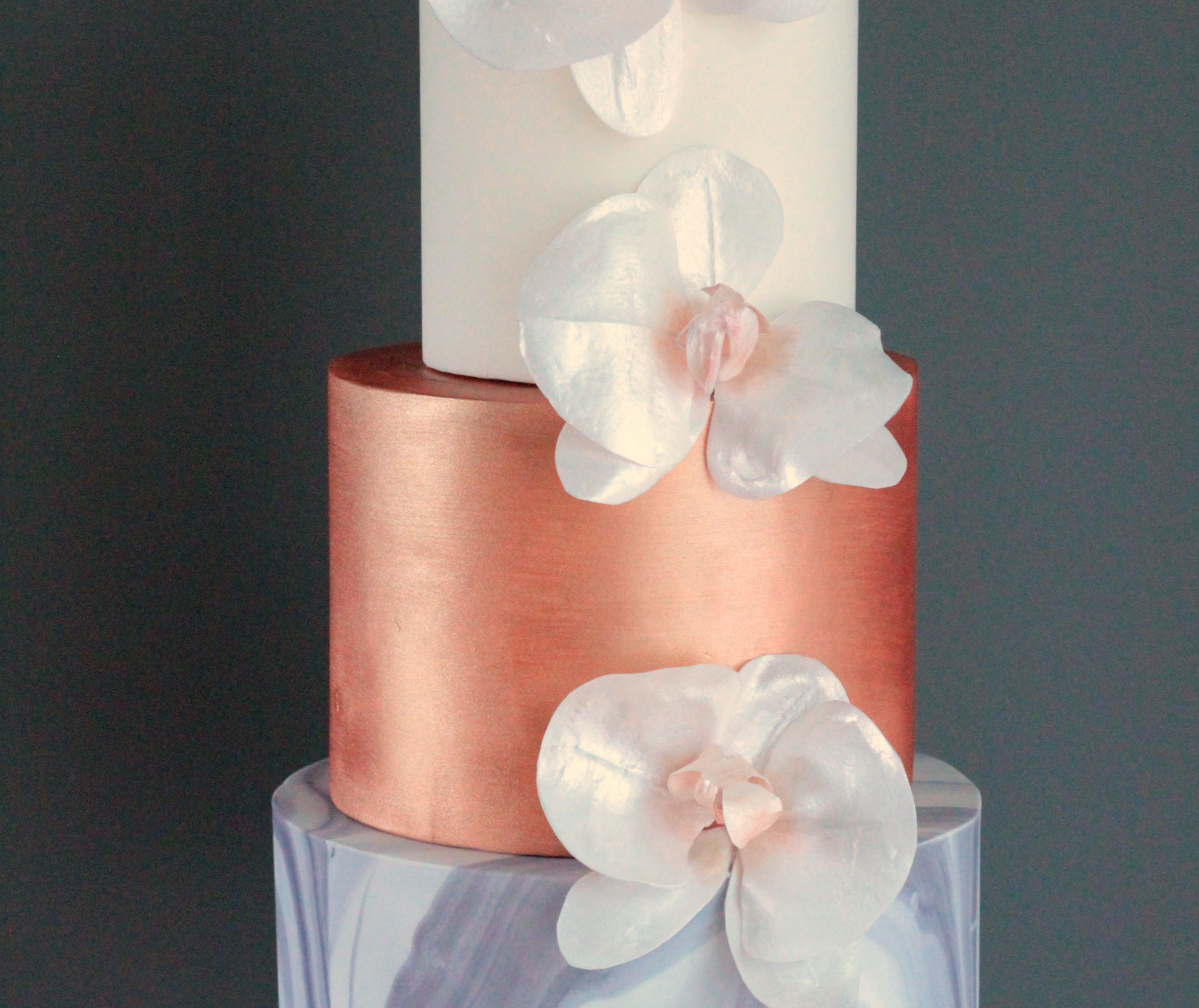 Marble fondant with hand painted bronze and wafer paper moth orchids.