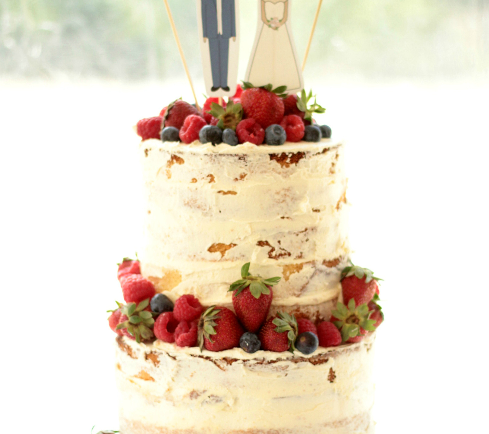Rustic buttercream with fresh seasonal berries for a casual wedding style.