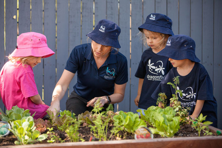 A teacher showing toddlers how to garden | Dragonfly's Childcare