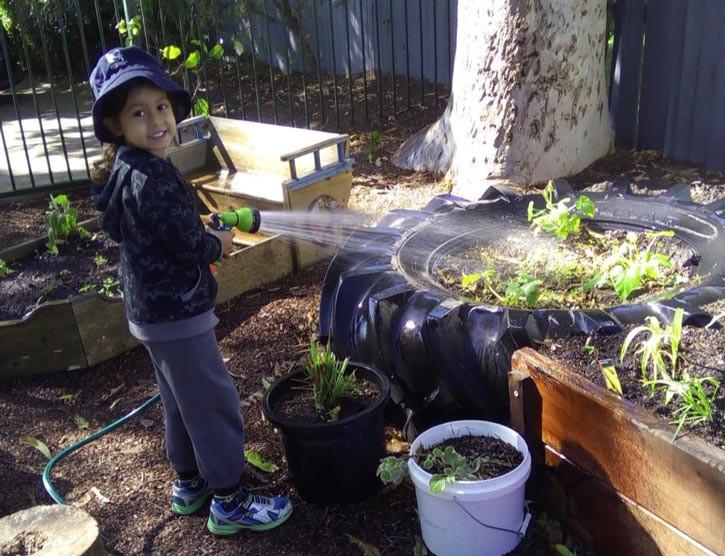 kid watering the plants