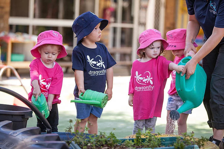 Toddlers in childcare centre watering the plants