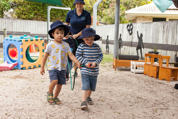 Young children carrying a water hose in a childcare centre