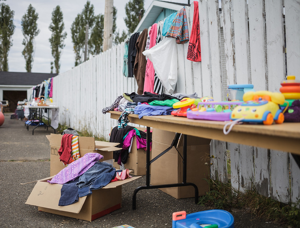 garage sale against fence selling toys