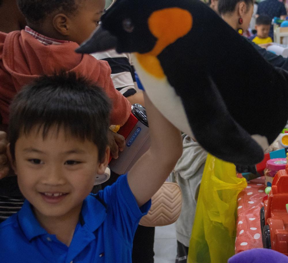 Boy carrying penguin around Joy of Giving's Toy Swap