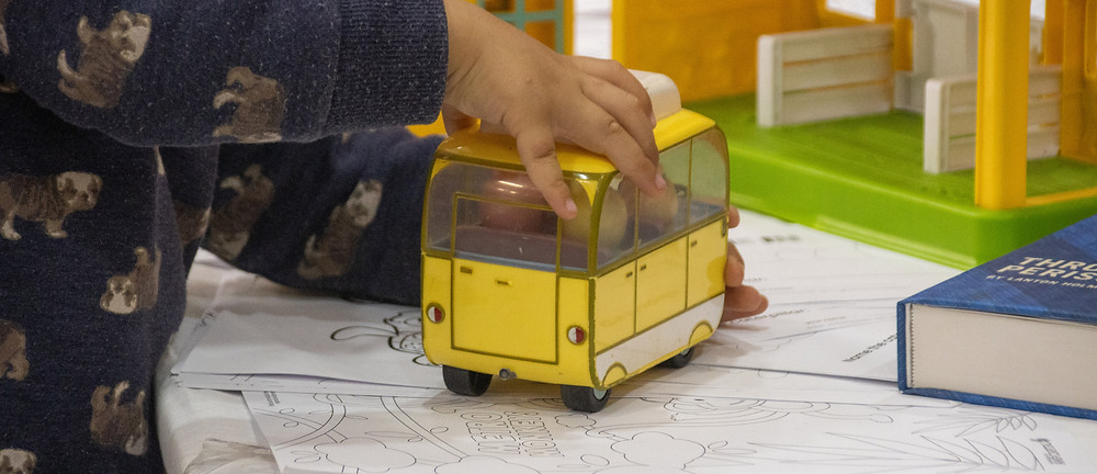 Boy playing with a toy bus