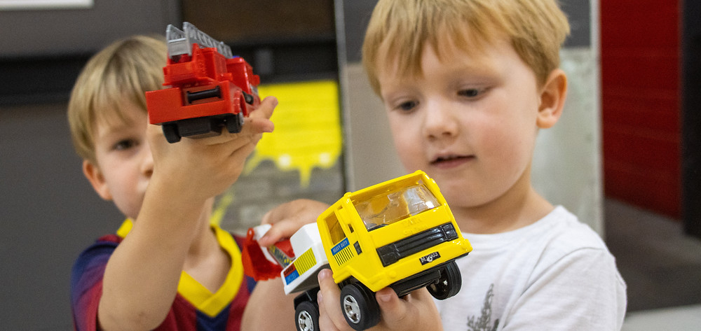 Two boys holding toy trucks