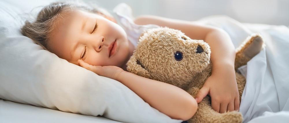 Girl cuddling her teddy bear in bed