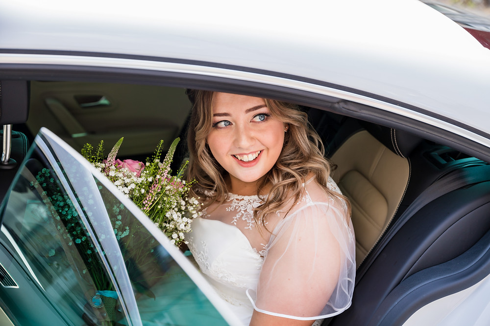A beautiful bride in the car that is taking her to the wedding ceremony