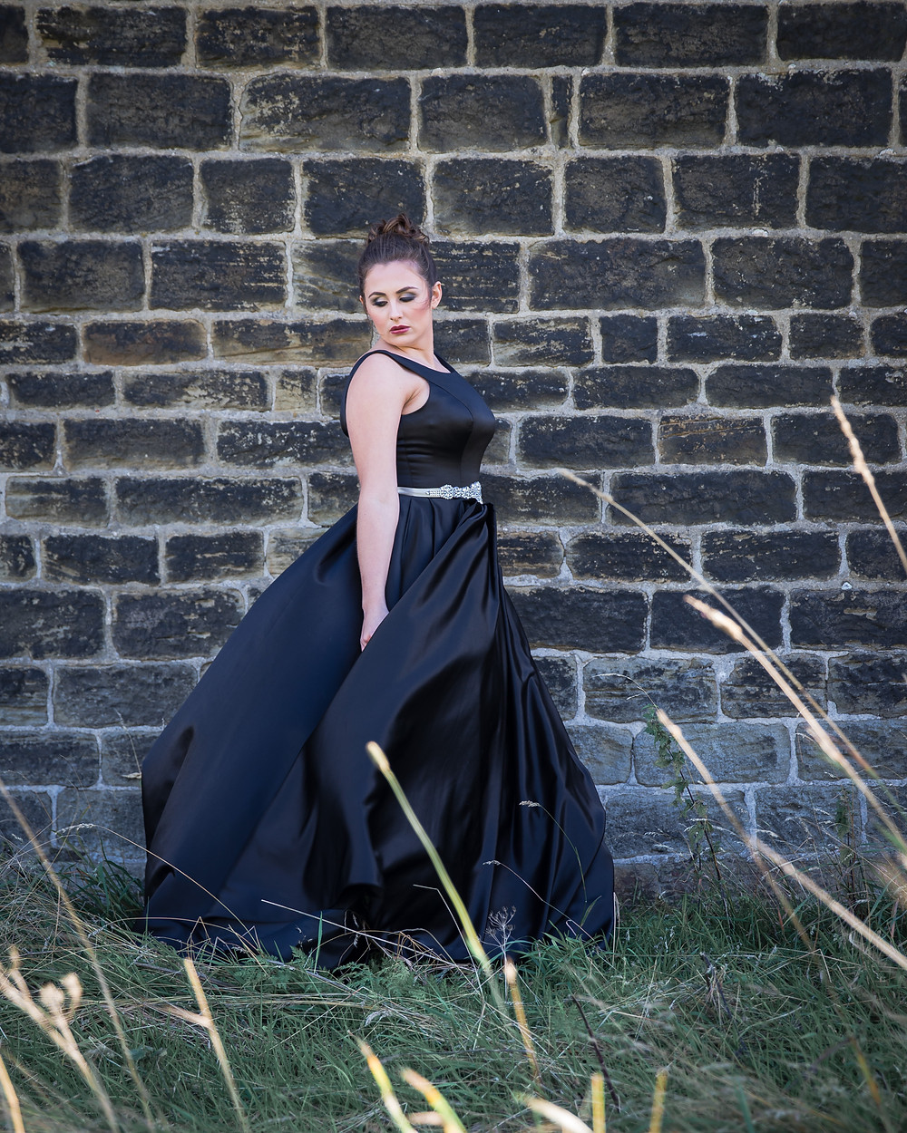 A model wearing black satin dress against a black brick wall